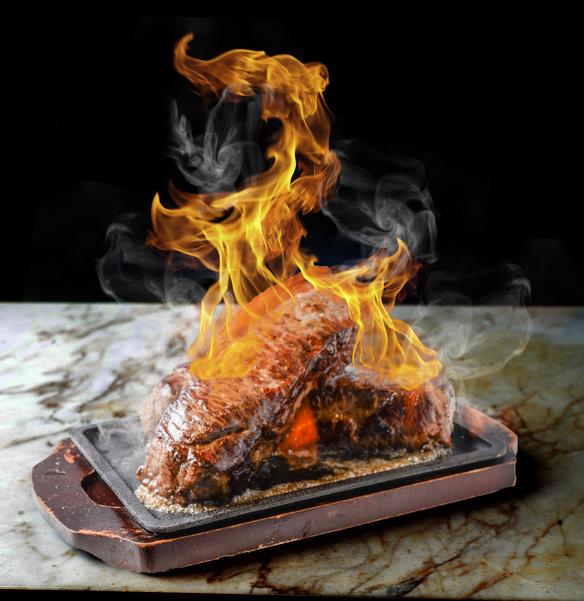 塊肉が目の前で燃え上がる!名物「ファイヤーステーキ」!鉄板アツアツの塊肉を、お客様の目の前で豪快にフランベ!高く燃え上がるファイヤーは、ステーキをより美味しく昇華させます! ※プレミアムプランのみの限定メニュー ※初回のみのご提供 ※お一人様200g×人数分のご提供(写真は4名様分)